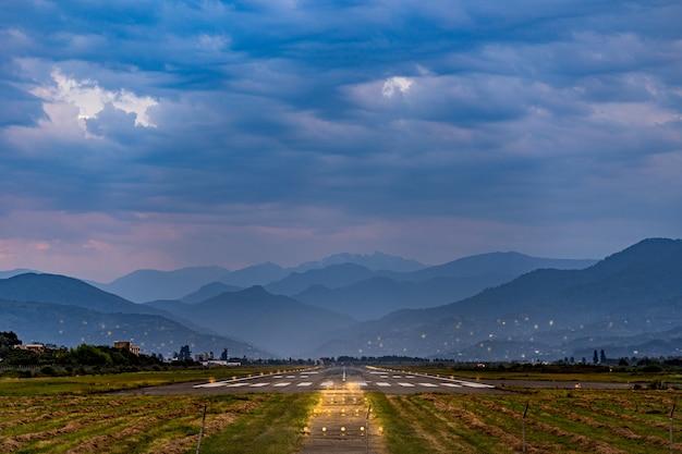 Baan op de luchthaven tegen de achtergrond van de bergen in de avond