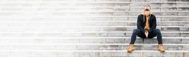 Baard knappe man op een trap buiten herfst straat