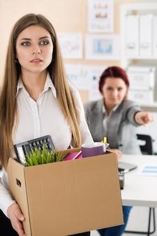 Baas die een werknemer ontslaat. neerslachtig ontslagen kantoormedewerker met een doos vol met haar bezittingen