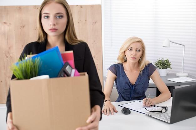 Baas die een werknemer ontslaat. neerslachtig ontslagen kantoormedewerker met een doos vol spullen. ontslagen worden concept.
