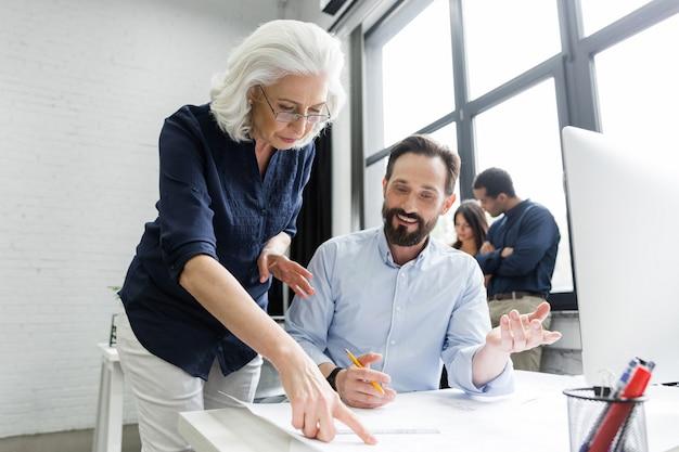 Baas die haar werknemer helpt met documenten