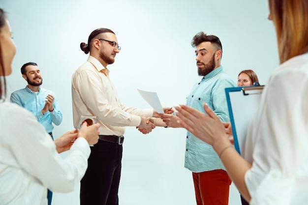 Baas die jonge succesvolle werknemer goedkeurt en feliciteert