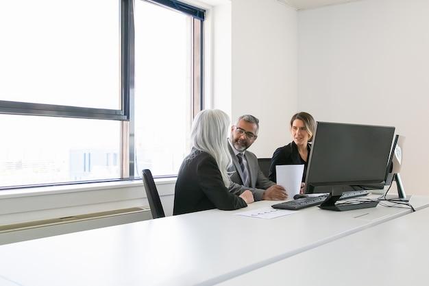 Baas en managers analyseren rapporten en bespreken werk. team zitten samen op de werkplek met monitoren, papieren en praten. kopieer ruimte. zakelijke bijeenkomst concept
