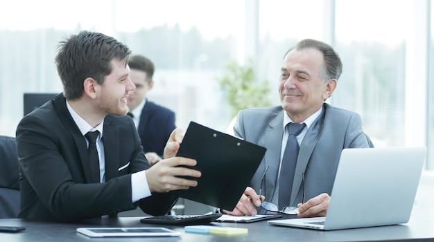 Baas en werknemer bespreken het document achter de balie