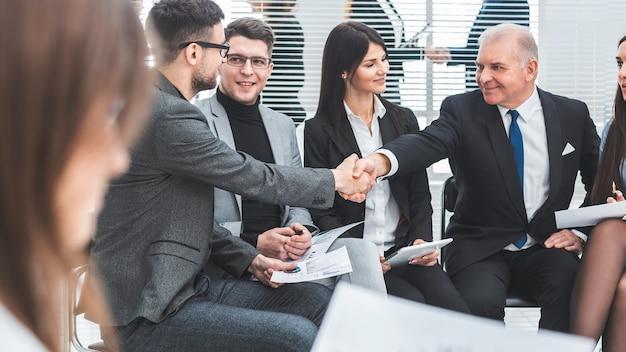 Baas handen schudden met een werknemer tijdens een werkvergadering. het concept van teamwerk