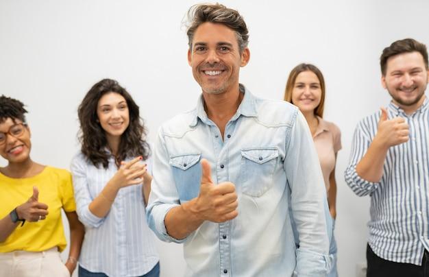 Baas in conworking maakt een goed gebaar dat mensen achter hem applaudisseren
