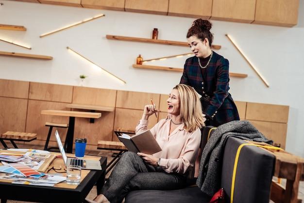Baas lachen. veeleisende vrouwelijke baas met rode lippen die lacht terwijl ze wordt gemasseerd door assistent