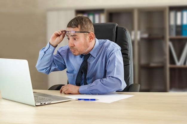 Baas zakenman aan zijn bureau kijkt verbaasd naar de laptop die zijn bril opheft