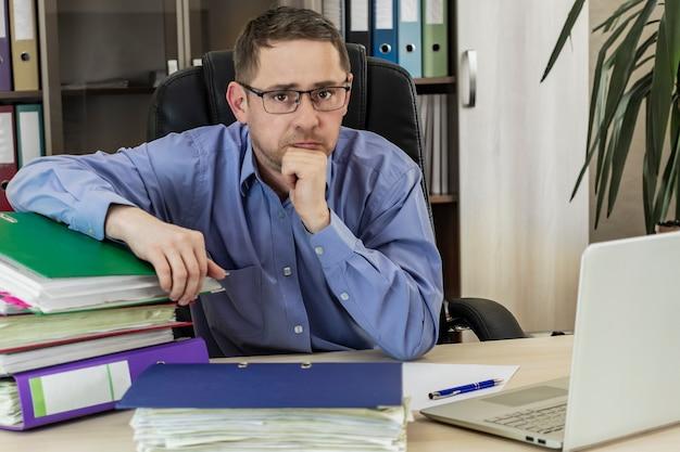 Baas zakenman aan zijn bureau op kantoor met een heleboel mappen met papieren