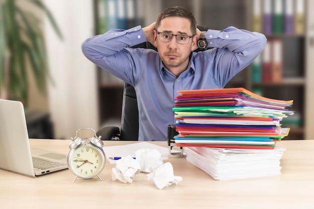 Baas zakenman aan zijn bureau op kantoor met een stapel mappen en verfrommeld papier