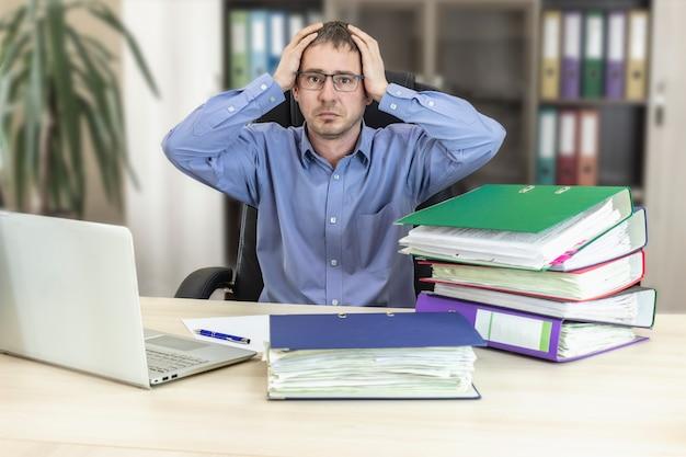 Baas zakenman aan zijn bureau op kantoor met een stapel mappen houdt zijn hoofd vast met zijn handen