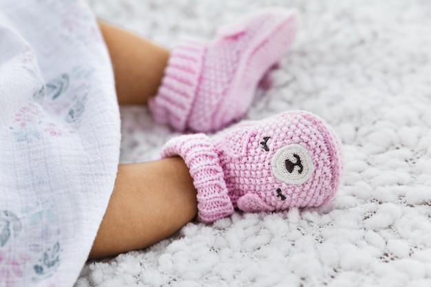 Babe meisje draagt roze gebreide schoenen, baby benen op een witte deken