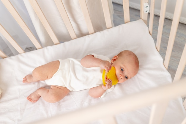 Baby 6 maanden oud meisje liggend in de wieg, ochtendbaby, baby naar bed gebracht, kleine baby kijkt door de wieg