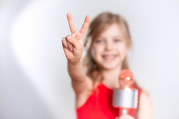 Baby 7 - 8 jaar oud, schattig charmant blond meisje met blond haar zingt in het apparaat, bluetooth microfoon en glimlacht op een grijze muur. ziet er cool uit met twee vingers