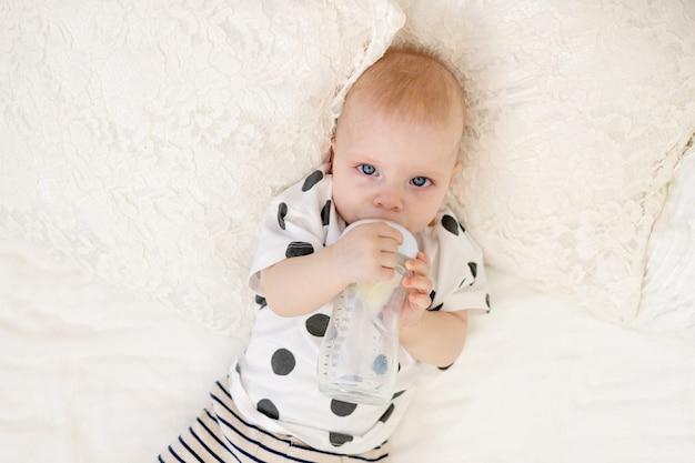 Baby 8 maanden oud liggend op het bed in pyjama's en consumptiemelk uit een fles, babyvoeding concept, bovenaanzicht, plaats voor tekst