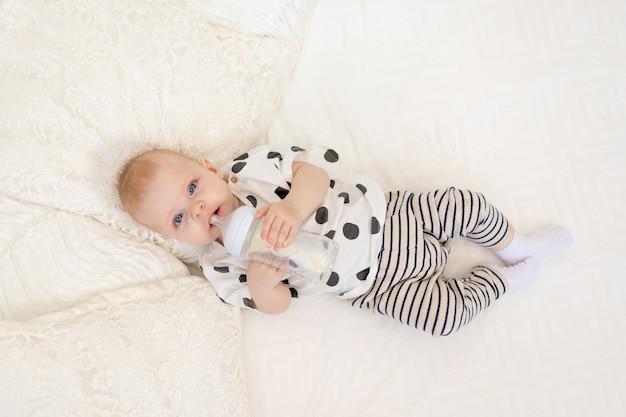 Baby 8 maanden oud liggend op het bed in pyjama's en consumptiemelk uit een fles, babyvoeding concept