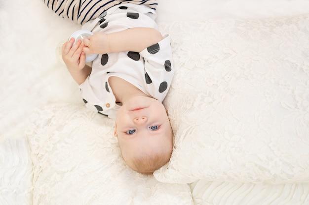 Baby 8 maanden oud liggend op het bed thuis in pyjama met een fles melk, babyvoeding concept, baby zuigmelk, plaats voor tekst