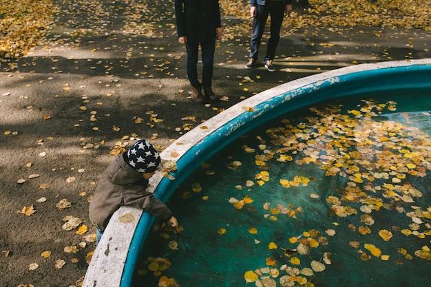 Baby aanraken van bladeren in het water herfst familie wandeling