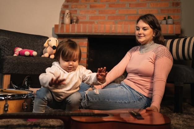 Baby babymeisje gitaar spelen met haar moeder.