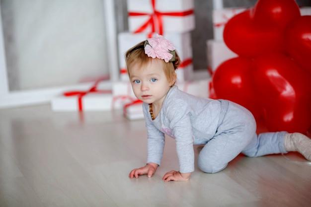 Baby babymeisje kruipen op haar knieën in een lichte kamer op de achtergrond op de achtergrond van ballonnen en witte dozen