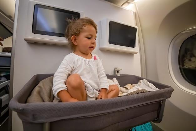 Baby-babymeisjeszitje in een speciale wieg in het vliegtuig, kijk naar de zijkant in de wieg in het vliegtuig