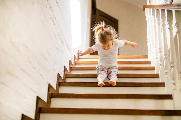 Baby blond meisje in wit t-shirt onderaan trappen binnenshuis, camera kijken en glimlachen.