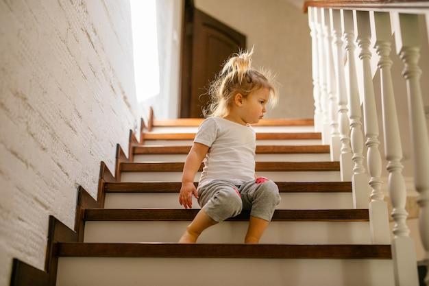 Baby blond meisje in witte t-shirt aan de onderkant van trappen binnenshuis, camera kijken en glimlachen