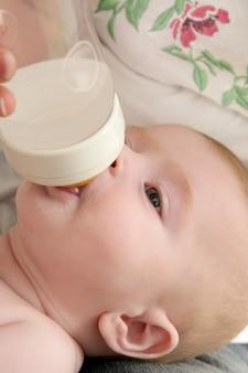 Baby blond meisje voedende consumptiemelk