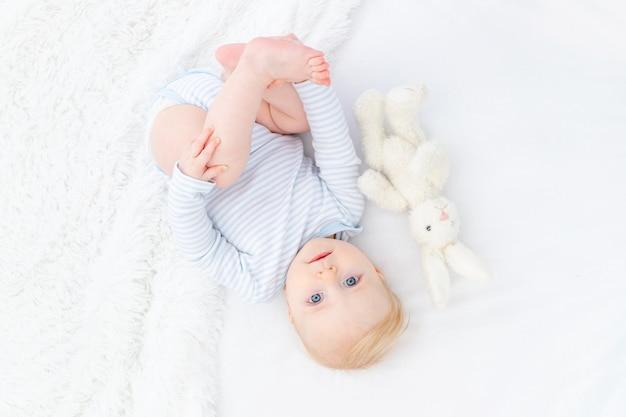Baby blonde jongen zes maanden oud op bed met speelgoed
