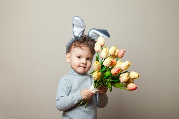 Baby boyin bunny oren met boeket van roze tulpen