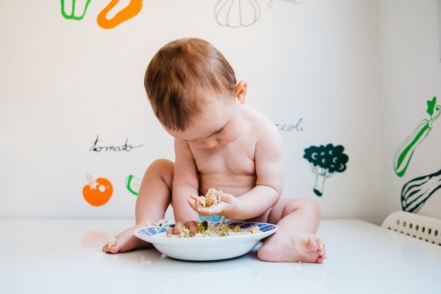 Baby die alleen eet en de baby-led weaning-methode doorneemt en de smaken van voedsel met nieuwsgierigheid onderzoekt.