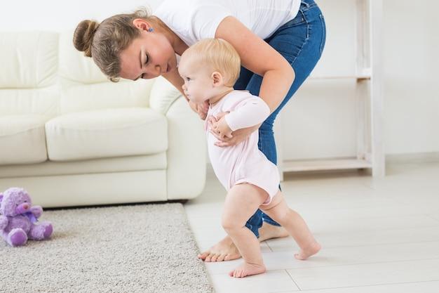 Baby die de eerste stapjes zet met de hulp van moeder thuis
