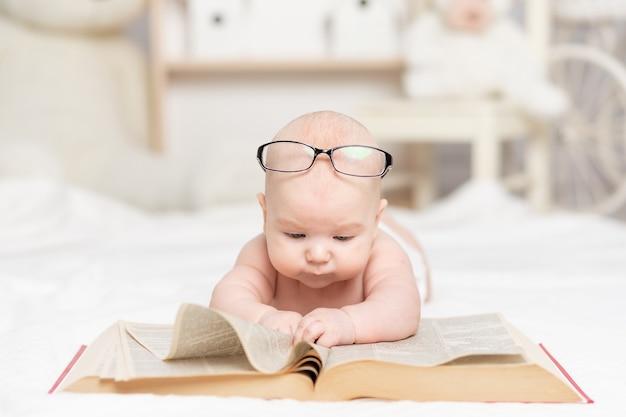 Baby die een boek leest of ernaar kijkt in het kinderdagverblijf, leer- en ontwikkelingsconcept