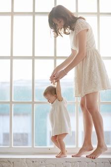 Baby die eerste stappen met de hulp van de moeder thuis zet. baby leunend wandelen met moeder