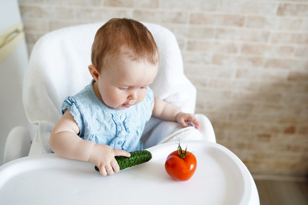 Baby die groenten eet. groene komkommer in meisjehand in zonnige keuken.