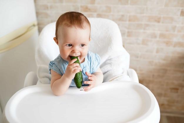 Baby die groenten groene komkommer op de keuken eet.