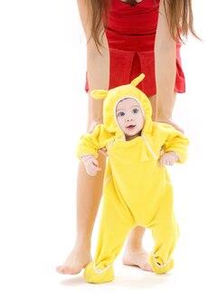 Baby die in geel pak de eerste stappen maakt