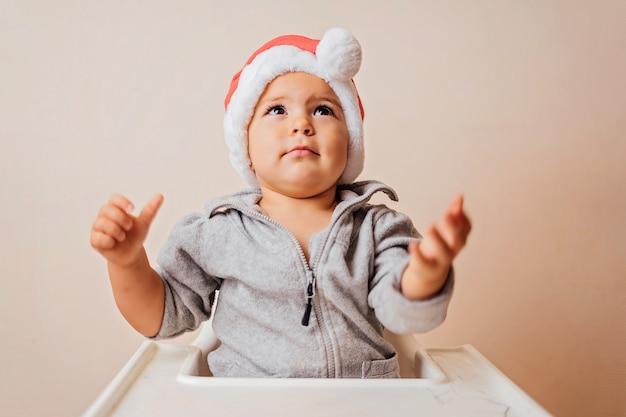 Baby die in kerstmisbonnet omhoog kijkt