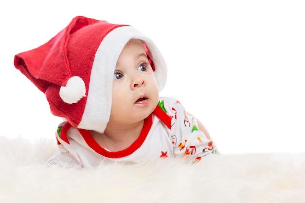 Baby die op zijn buik in een santa claus-hoed met verrast ligt