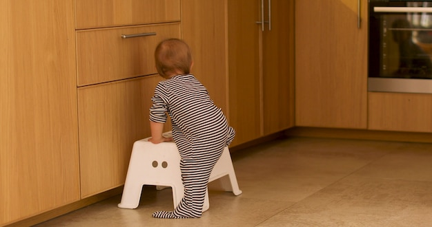 Baby die stapkruk in keuken beklimt