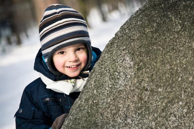 Baby die van achter de steen kijkt