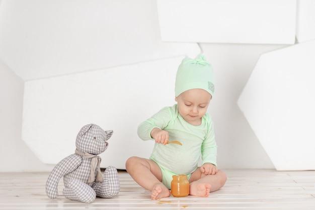 Baby eet alleen uit een potje, het concept van voeding en babyvoeding