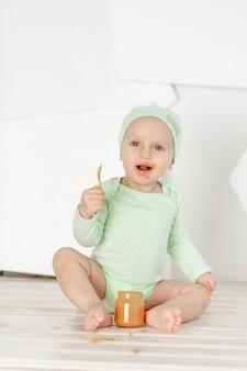 Baby eet fruitpuree met een lepel in een groen rompertje, voeding en babyvoedingconcept