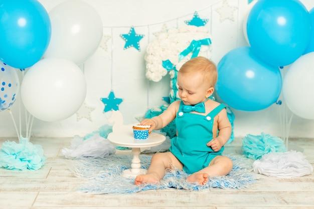Baby eet verjaardagstaart en viert eerste verjaardag in fotozone in blauwe kleur met ballonnen en cake