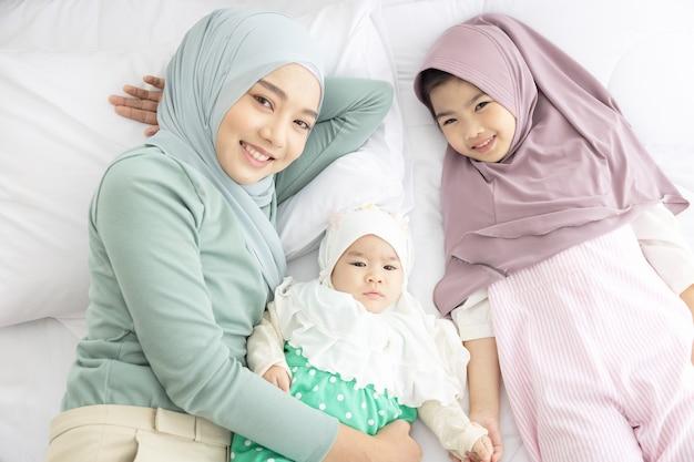 Baby en moeder thuis in bed, gelukkige liefdevolle familie