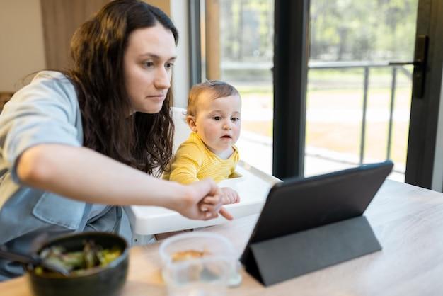 Baby en ouders bezig met digitale gadgets tijdens een lunch thuis