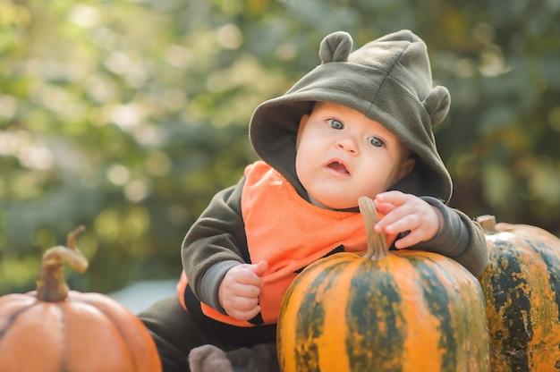 Baby en pompoenen in de natuur. grappig klein kind voor halloween en pompoenen