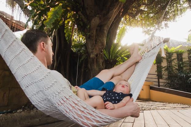 Baby en vader slapen in een hangmat