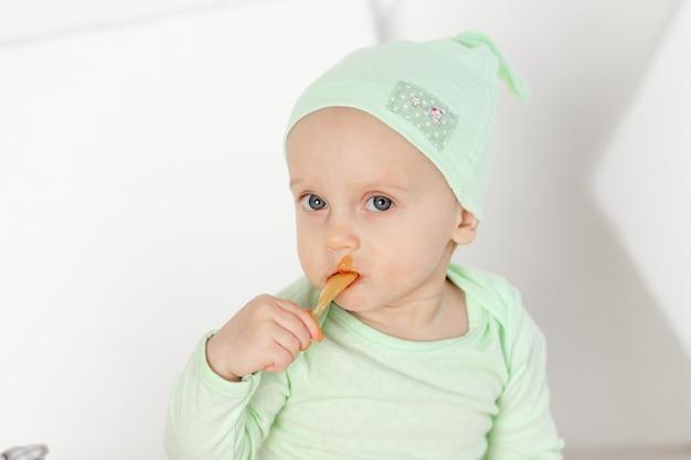 Baby eten fruit puree lepel in groen romper, portret, voeding en babyvoeding concept