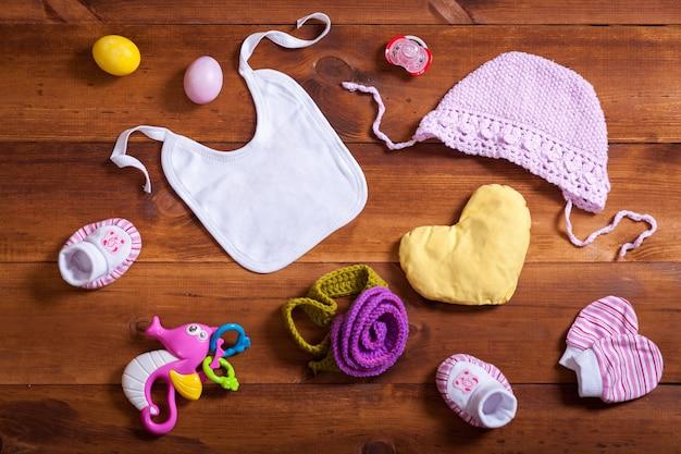 Baby gebreide kleding ingesteld op bruin houten tafel, bovenaanzicht plat lag